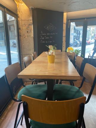 Une table en bois avec des chaises de bar en velour vert, un mur ardoise, un cadre chaleureux. la salle du bas est lumineuse et donne sur la cuisine ouverte