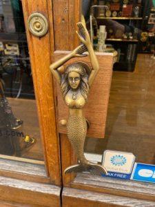 la poignée de la porte de la boutique est une sculpture métallique de sirène, dans un doré usé.
