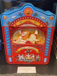 Une boite à musique bleu et rouge, reproduction d'époque, avec des personnages comiques du cirque.