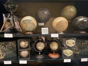 Une collection de globes de petite taille et de différentes couleurs, fixées sur plusieurs sortes de socles et supports.
