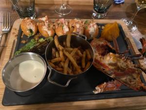 l'un des plats signature un demi-homard grillé, servi des minis sandwichs de homard, des frites maisons, une purée de patates douces et de la laitue braisée