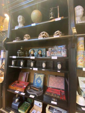 Bougies, crânes, globes, et coffrets ornent les étagères en bois.